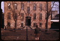 Urchin looks at old 3-story tenement set far back in low yard